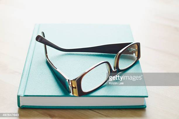 studio shot of spectacles on book - things that go together stock photos and pictures