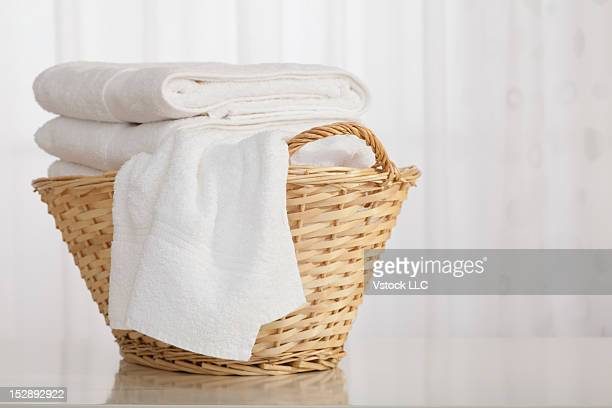studio shot of stack of white towels in wicker basket - タオル ストックフォトと画像