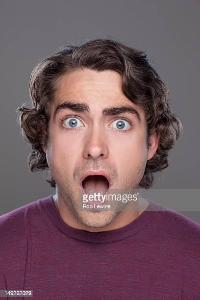 Studio shot of surprised young man
