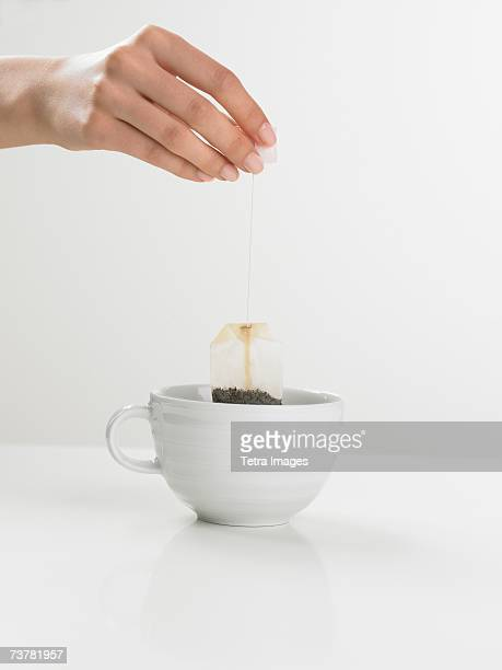 Studio shot of tea cup with woman's hand holding tea bag