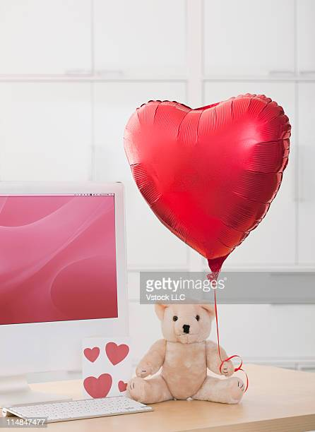 Studio shot of teddy bear holding heart-shaped balloon by computer