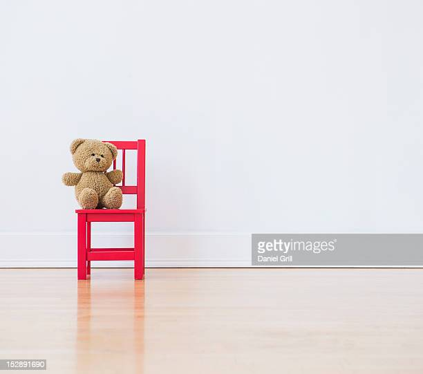 Studio shot of teddy bear sitting on red chair