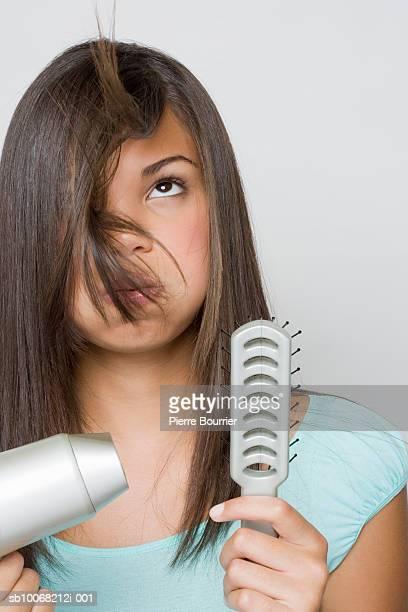 Studio shot of teenage girl (16-17) blowing up hair