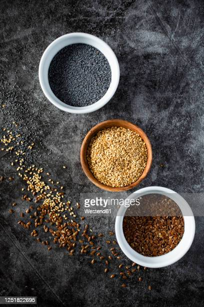 studio shot of three bowls with sesame, flax and poppy seeds - sesame stock pictures, royalty-free photos & images