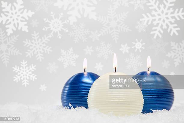Studio shot of three candles with snow flakes in background