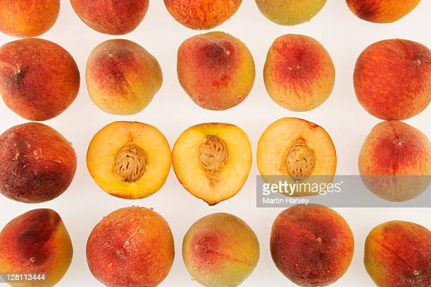 Studio shot of three fresh halved peaches with pits arranged with whole peaches