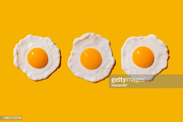 studio shot of three fried eggs - three objects stock pictures, royalty-free photos & images