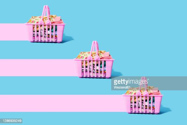 studio shot of three pink shopping baskets filled with clothing leaving pink trails - fast fashion stock pictures, royalty-free photos & images