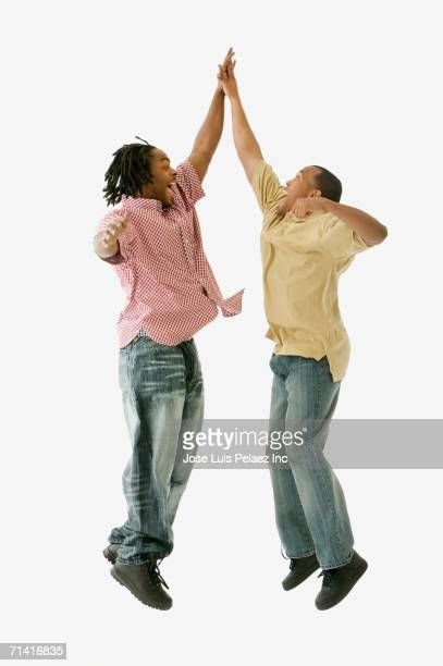 Studio shot of two African men high fiving in mid-air