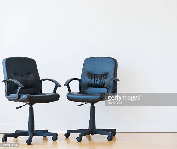 studio shot of two black office chairs - dois objetos - fotografias e filmes do acervo