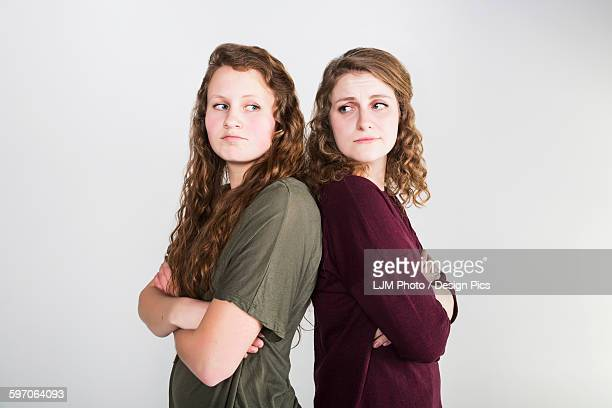 studio shot of two girlfriends fighting, on a white background - sister stock photos and pictures