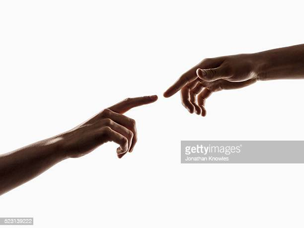 Studio shot of two human hands, touching fingers, white background