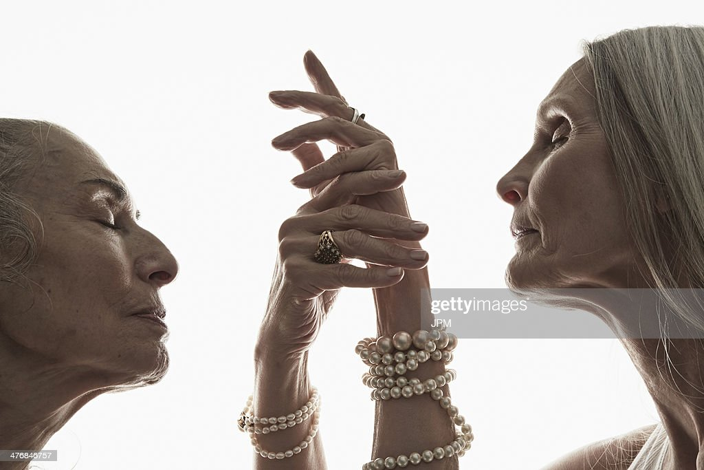 Studio shot of two mature women in profile with eyes closed : Stock Photo