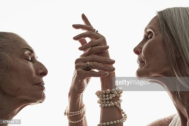 studio shot of two mature women in profile with eyes closed - brazalete pulsera fotografías e imágenes de stock
