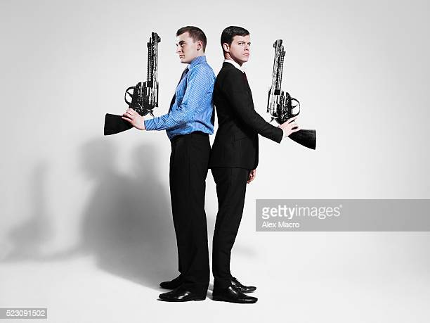 Studio shot of two men standing back to back and holding large guns
