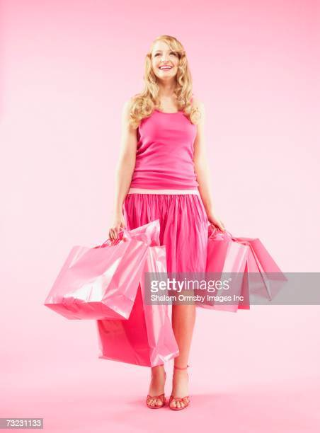 Studio shot of woman carrying shopping bags and smiling