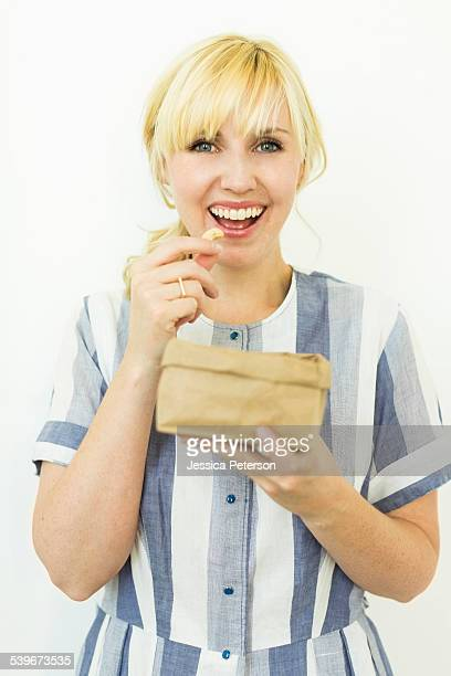 Studio shot of woman eating cashews from paper bag