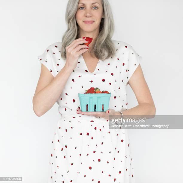 studio shot of woman holding basket of strawberries - alleen één oudere vrouw stockfoto's en -beelden