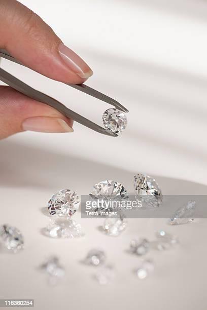 studio shot of woman holding diamonds - groupe moyen d'objets photos et images de collection