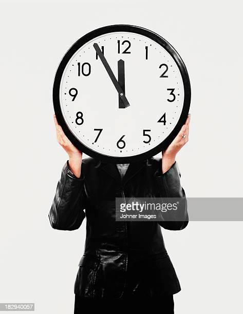 Studio shot of woman holding large clock
