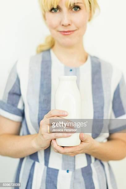 Studio shot of woman holding milk bottle