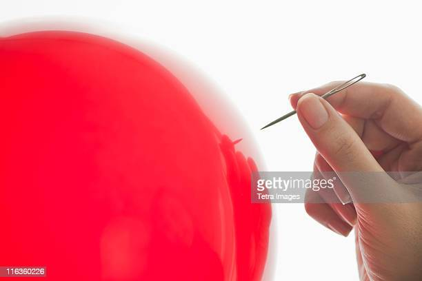 studio shot of woman holding needle close to red balloon - sewing needle stock pictures, royalty-free photos & images