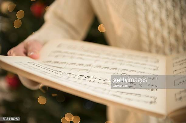 Studio Shot of woman holding sheet music at christmas