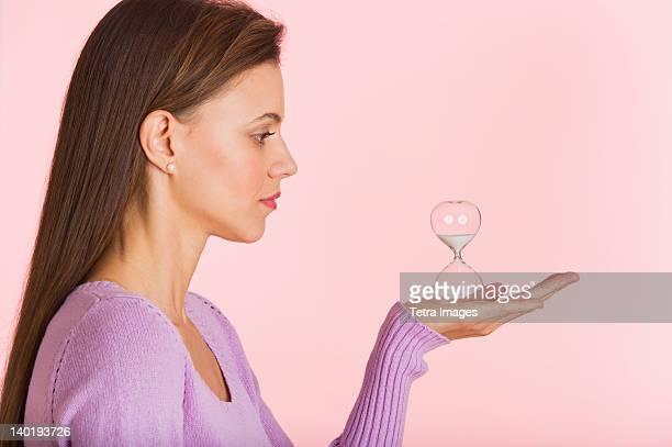 Studio shot of woman holding small hourglass