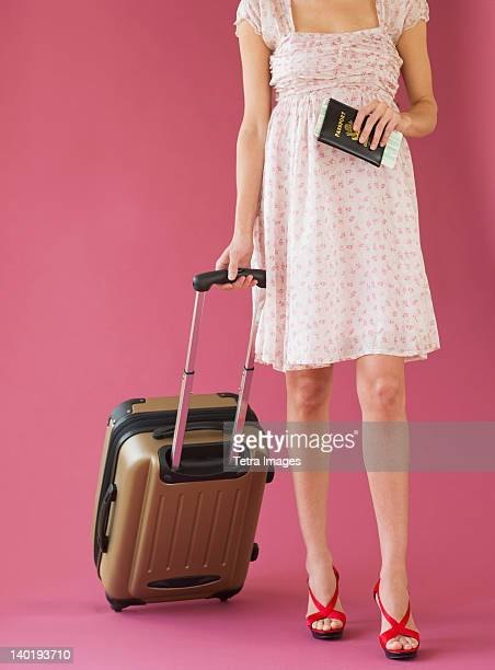 Studio shot of woman holding suitcase and passport
