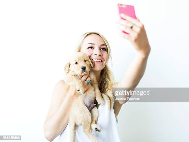 Studio shot of woman photographing self with Golden Retriever puppy
