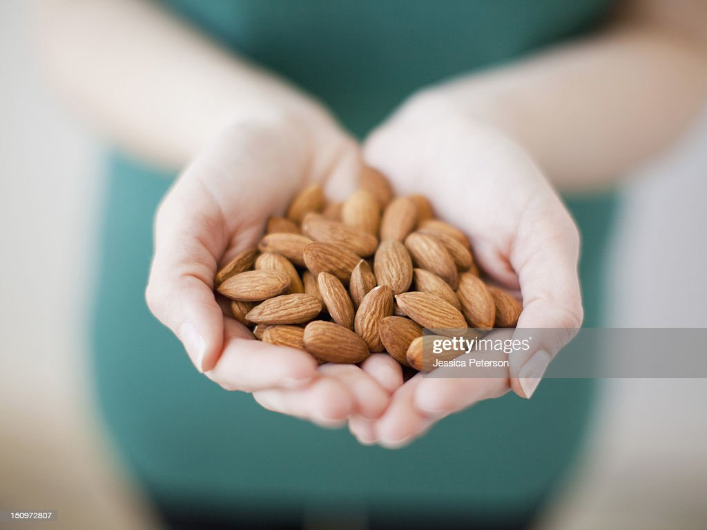 Studio shot of woman showing handful of almonds : Stock Photo