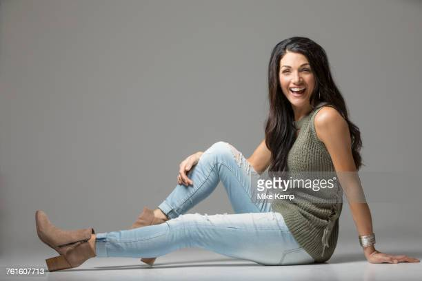 Studio shot of woman sitting on floor and laughing