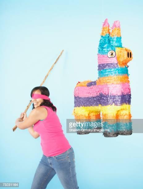 Studio shot of woman swinging stick at pinata
