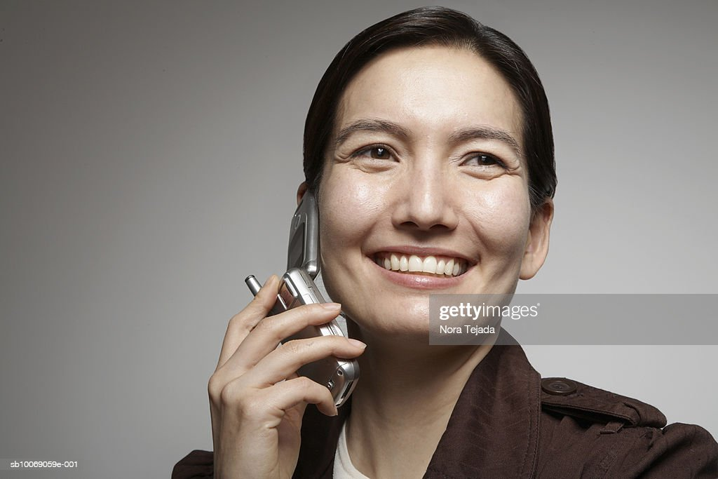 Studio shot of woman talking on mobile phone : Stockfoto