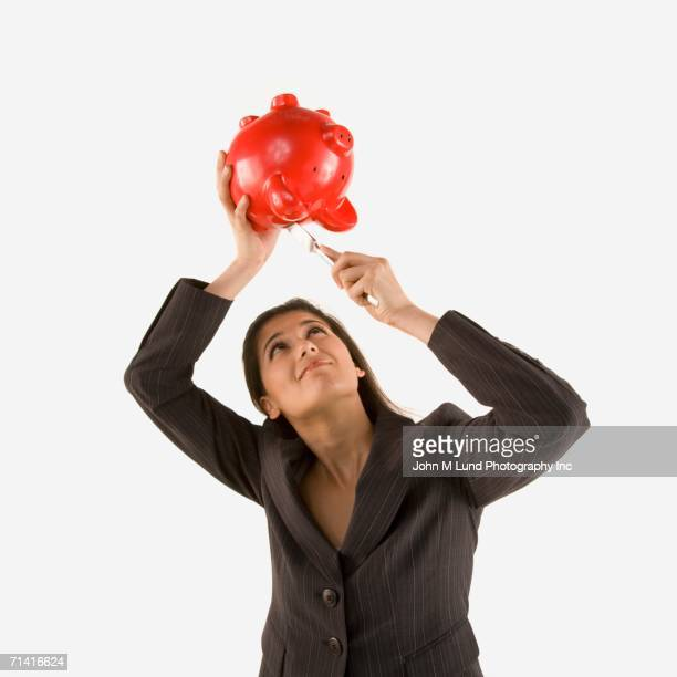 Studio shot of woman trying to get money out of piggy bank