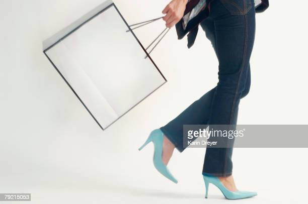 Studio shot of woman walking with shopping bag