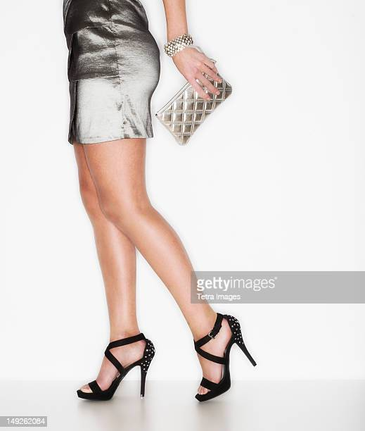 studio shot of woman wearing mini dress and stilettos - gray purse stock pictures, royalty-free photos & images