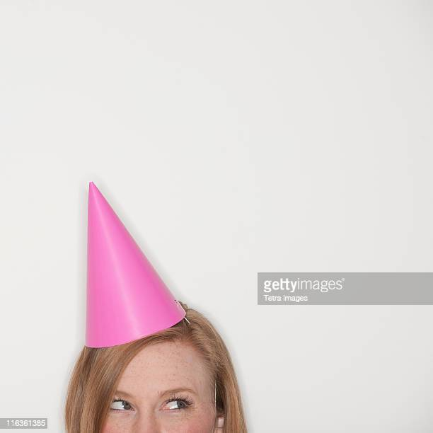 Studio shot of woman wearing pink party hat