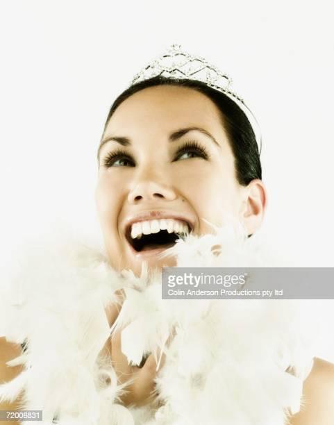 Studio shot of woman wearing tiara and feather boa