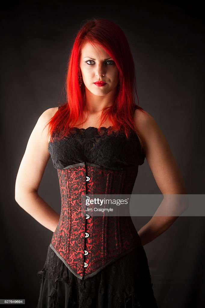 Studio Shot Of Woman With Dyed Red Hair Wearing Retro Style Dress