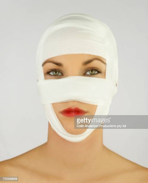 Studio shot of woman with plastic surgery bandages on head