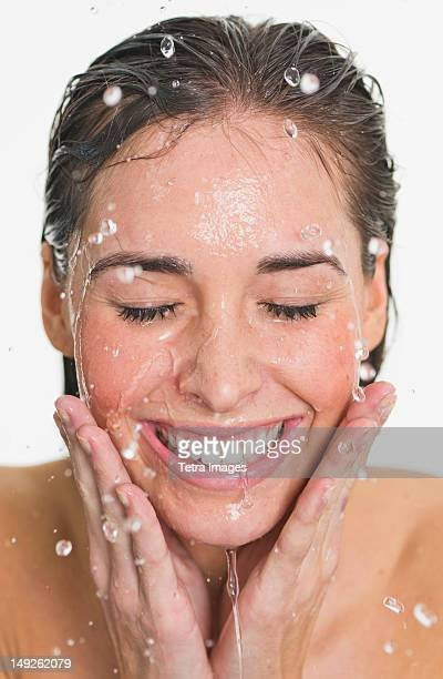 Studio shot of woman with splash of water on face