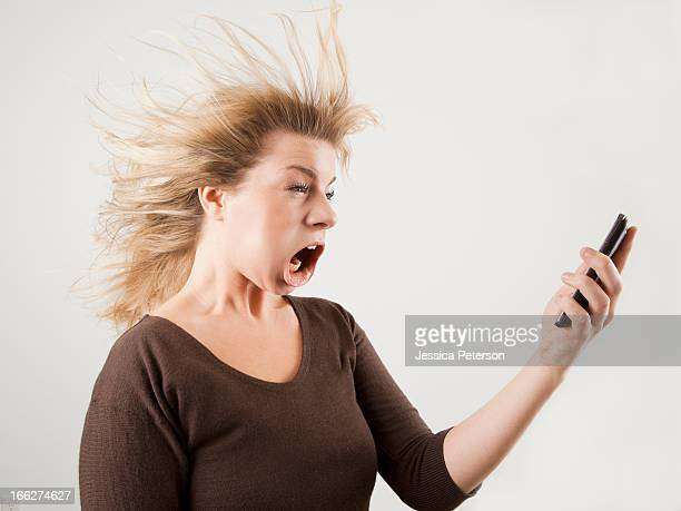Studio shot of woman with windblown mouth holding phone