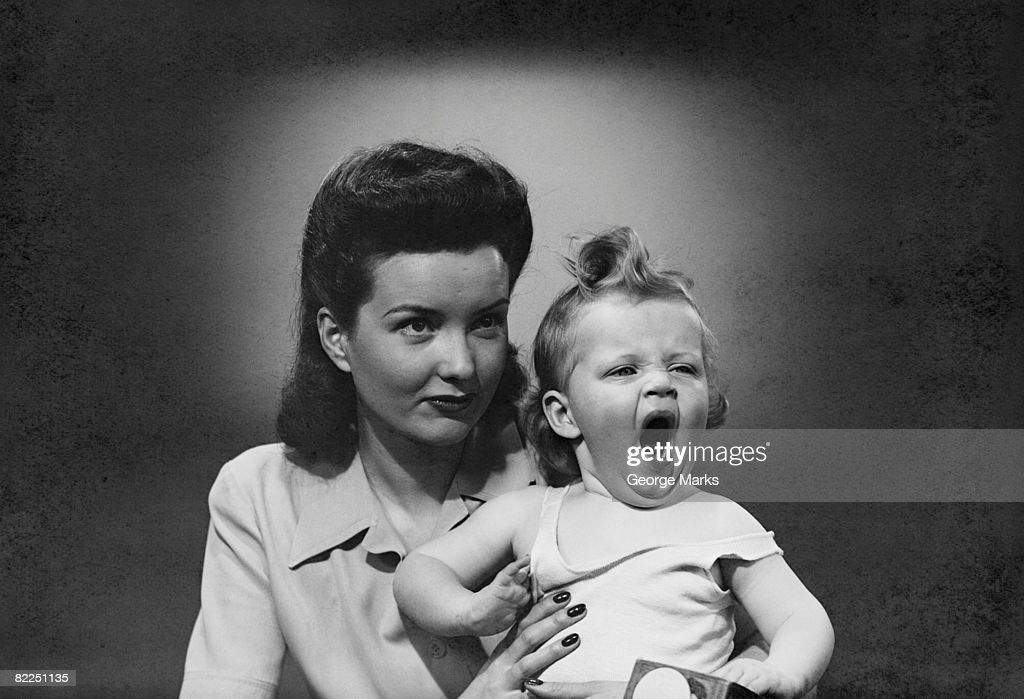 Studio shot of woman with yawning baby girl (6-11 months) : Stock Photo