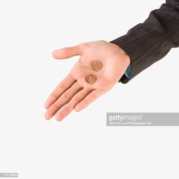 Studio shot of woman's hand holding two pennies
