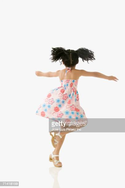 Studio shot of young African girl twirling