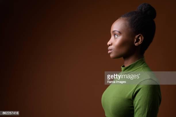 Studio shot van jonge mooie Afrikaanse Zulu zakenvrouw dragen groene outfit tegen gekleurde achtergrond