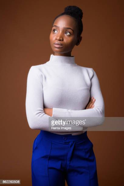 Studio shot of young beautiful African Zulu businesswoman wearing white turtleneck sweater against colored background