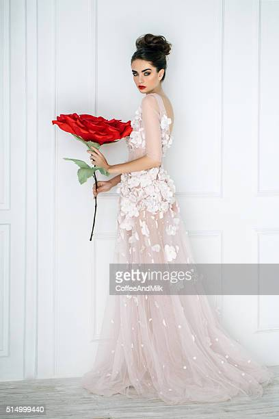Studio shot of young beautiful bride with big rose