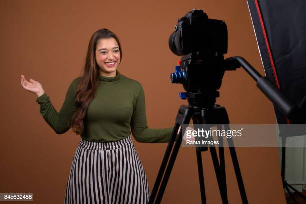 Studio shot of young beautiful Indian woman vlogging against colored background